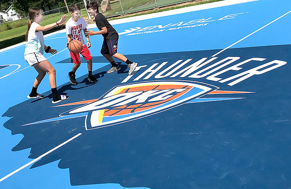 KEVIN HARVISON  <br /> Pictured from left, Alexas Lizik guards Davonte Jones as he tries to dribble past Jonathan Lizik while enjoying the new Thunder Court at Chadick Park.