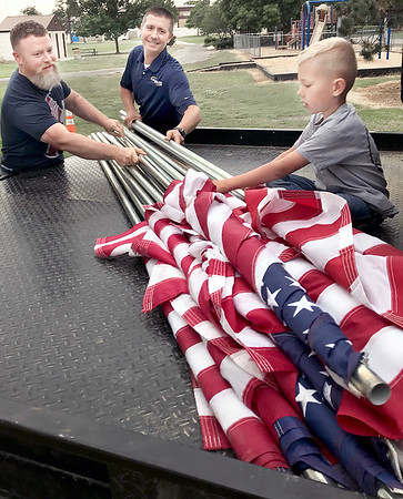 KEVIN HARVISON |<br /> Pictured from left, Josh Hass, Sayer Brenner and Austen Brenner load U.S. Flags from the Rotary House to be displayed Friday morning.