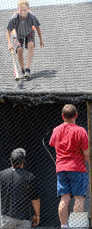 KEVIN HARVISON | Staff photo<br /> A young fan helps retrieve a bat slung on top of the club house at third base during Junior Sunbelt action Tuesday at Mike Deak Field.