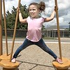 KEVIN HARVISON | Staff photo<br /> Camilla Conway stretches out while on some playground equipment recently.