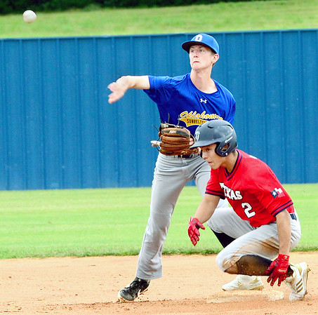 KEVIN HARVISON | Staff photo<br /> Oklahoma Blue shortstop attempts to turn two during opening day action of the Junior Sunbelt Classic against Texas at Eastern Oklahoma State College Friday.