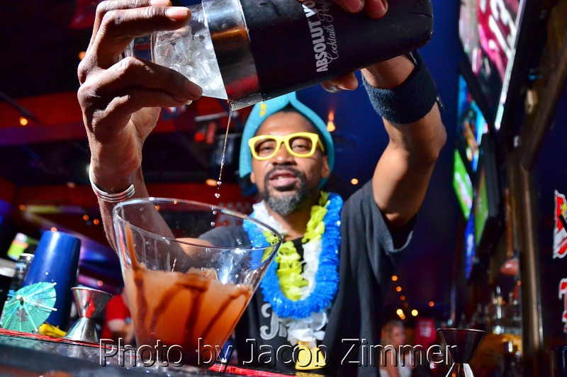 Bartender Ron Wells pours a mixed drink at the Sports and Social Club's Beach Party Saturday night. July 14, 2013.