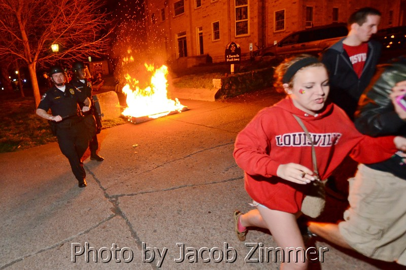 Students are chased away from a burning mattress on Third Street a few blocks north of UofL's Campus early Tuesday morning following the Louisville victory in the NCAA Championship. April 9, 2013.
