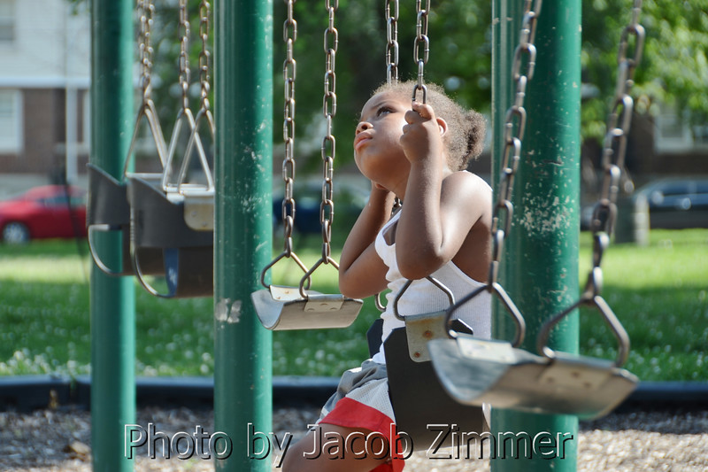 Demetrice Flint, 5, looks to the sky as he sits alone on the swing set outside the Baxter Square Community Center at Beecher Terrace. Wednesday, June 25, 2014.
