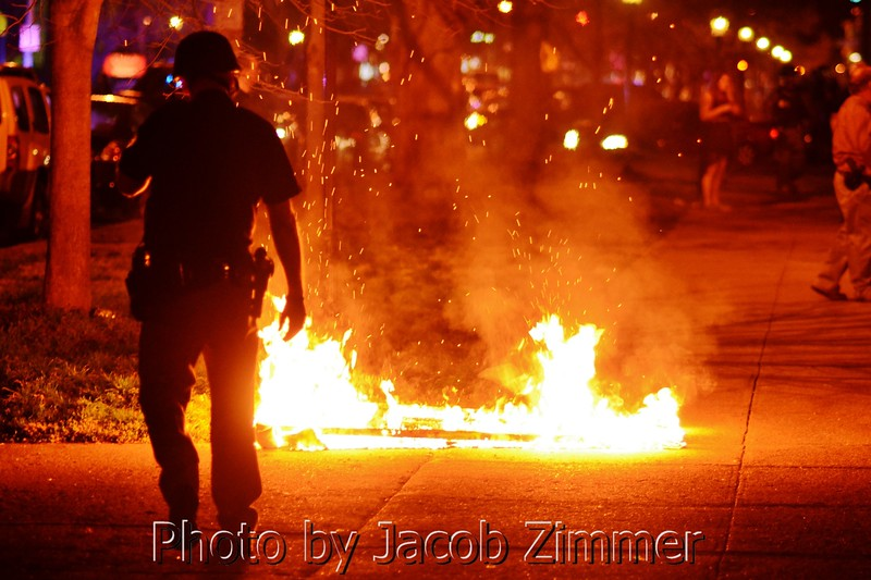 A police officer keeps a watchful eye on a burning mattress on Third Street a few blocks north of UofL's Campus early Tuesday morning following the Louisville victory in the NCAA Championship. April 9, 2013.