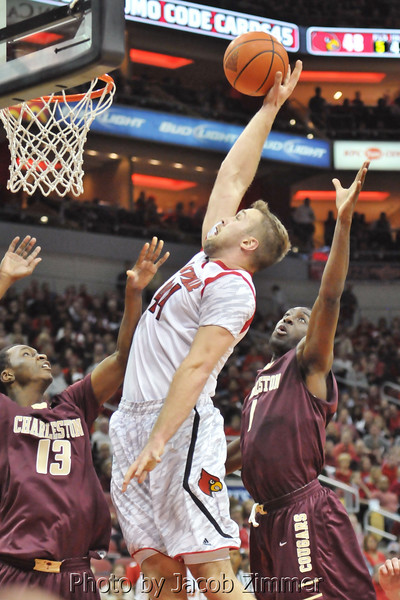 Louisville's Stephan Van Treese scores a dunk over Charleston defenders during the second half of the regular season opener against Charleston at the KFC YUM! Center Saturday. UofL defeated College of Charleston 70 to 48.  November 9, 2013.