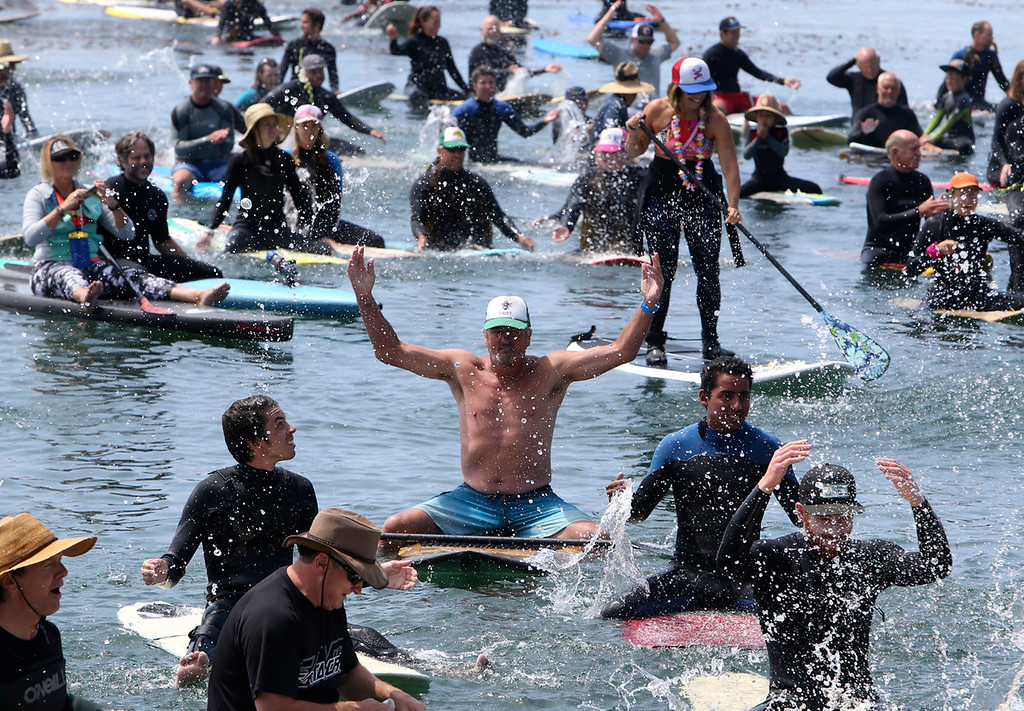 . Surfers splash in the water near Pleasure Point in Santa Cruz on Sunday morning during a paddle-out ceremony for Jack O\'Neill. (Kevin Johnson -- Santa Cruz Sentinel)