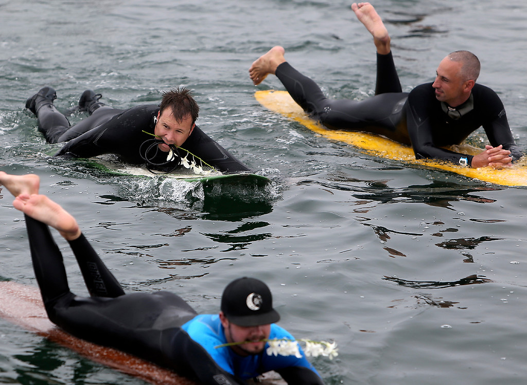 . Surfers hold flowers between their teeth as they paddle-out in honor of surfing pioneer Jack O\'Neill near Pleasure Point in Santa Cruz on Sunday. (Kevin Johnson -- Santa Cruz Sentinel)