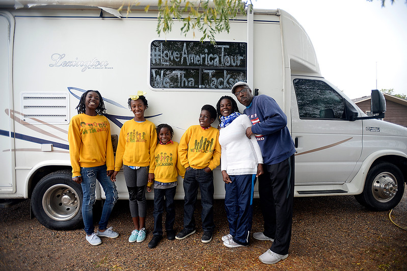 "The Jackson family pose for a photo Monday, Oct 2, 2017, near the RV that was loaned to them to use for part of their ""Love America Tour"". From left are K'rah Jackson, 16, Kyilah JAckso, 13, R'san Jackson, 7, K'shan Jackson, 11, Casaundra Jackson and Alan ""Pops"" Jackson.  The Texas family is visiting the Loveland area as part of its journey to take their children to all 50 U.S. states via bus or train. All that is left are Hawaii and Alaska for the home school family.  <br /> (Photo by Jenny Sparks/Loveland Reporter-Herald)"