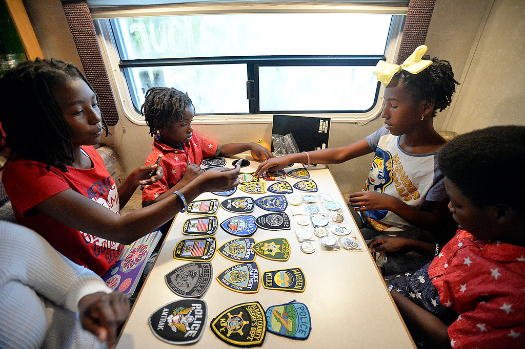". K\'rah Jackson, 16, left front, R\'san Jackson, 7, left back, Kyilah Jackson, right back, and K\'shan Jackson, 11, right front,  display the different police badges and challenge coins Monday, Oct 2, 2017, that they have collected while traveling the United States on their ""Love America Tour\"". The Texas family is visiting the Loveland area as part of its journey to take their children to all 50 U.S. states via bus or train. All that is left are Hawaii and Alaska for the home school family.   (Photo by Jenny Sparks/Loveland Reporter-Herald)"