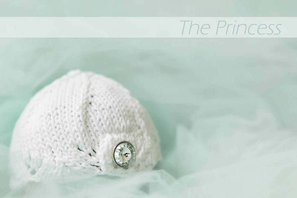 The Princess knit beanie has a scalloped edge and a rhinestone button.