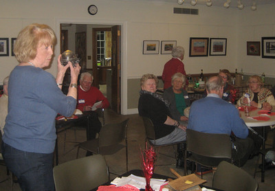 Jackie Johnson describing table artifacts from the Society's collections. A butter dish. Winter Potluck. February 15, 2015.