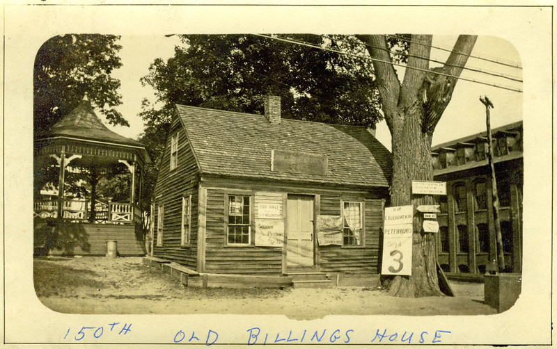 This house was erected on the common at Main and North Streets for the sesqui-centennial. (Exactly why is a mystery.) The tree is the Town Elm. Behind to the right are the Jaffrey Mills.