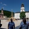 Auf dem Weg zum Stift St. Peter überqueren wir den Residenzplatz. Rechts hinten die von Fürsterzbischof Wolf Dietrich von Raitenau von 1588 an erbaute Neue Residenz. Wolf Dietrich war durch das Salz zum reichsten Fürsten im Deutschen Reich geworden. Dem Residenzplatz, der Neuen Residenz, dem neuen Dom bzw. dem freien Blick des Fürsten mussten 55 Bürgerhäuser und der Domfriedhof weichen. Nach einem Familienzwist diente der Bau nicht mehr als Sitz der Familie,  das Gebäude wurde öffentlichen Zwecken zugeführt. Heute beherbergt der Bau vor allem das Salzburg-Museum und das Salzburger Heimatwerk. Berühmt ist auch das Glockenspiel.Die Michaelskirche links ist die älteste heute noch bestehende Kirche der Stadt und geht auf das Jahr 780 zurück.