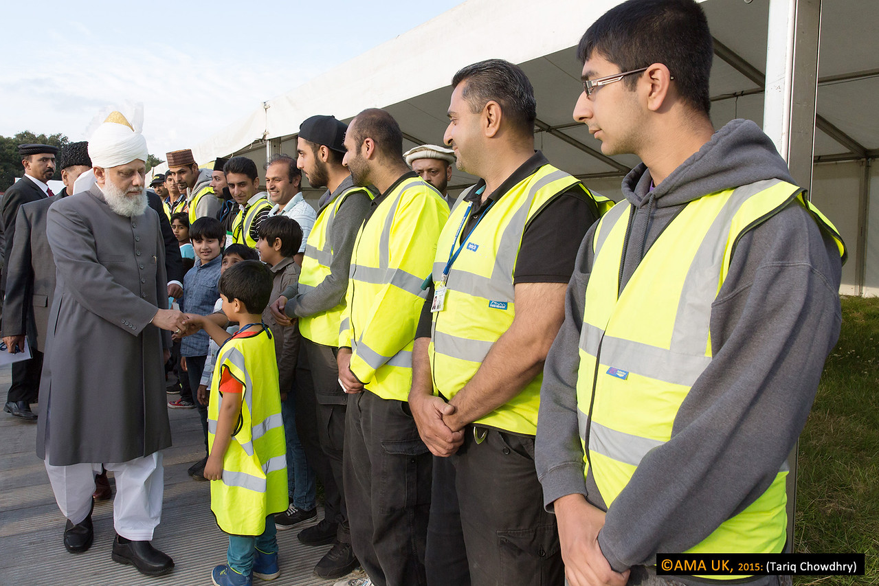 Young and old volunteers of the Jalsa line up to meet Huzur