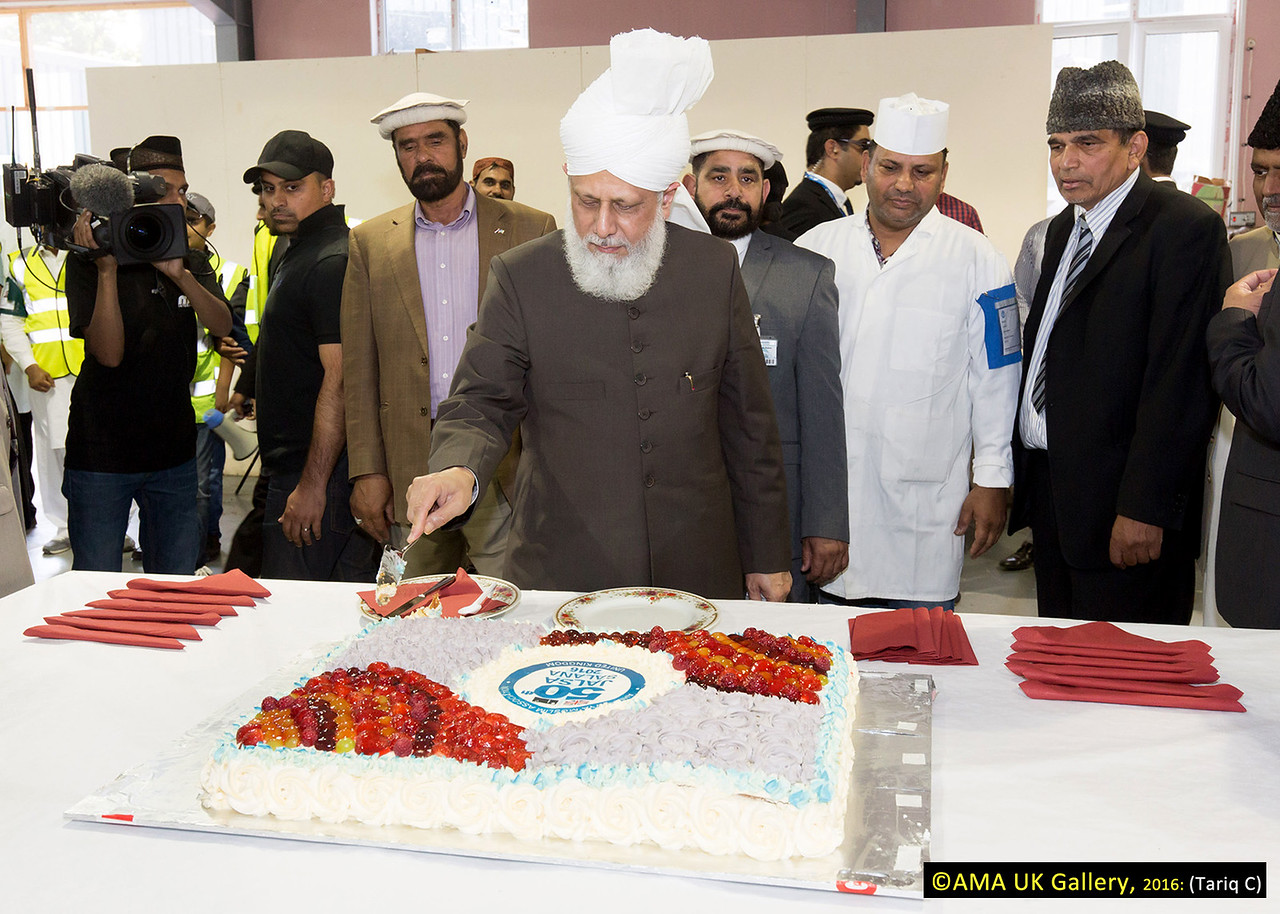 During the inspection, Hazrat Mirza Masroor Ahmad visited the various departments tasked with organising and running the three-day event. His Holiness was briefed on the arrangements as he inspected the site. His Holiness cutting the cake that marks the 50th Jalsa Salana UK.