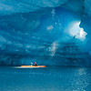 Kayaker paddles in beam of light and water melting from inside an iceberg cavern at Bear Lake, Kenai Fjords National Park, Alaska