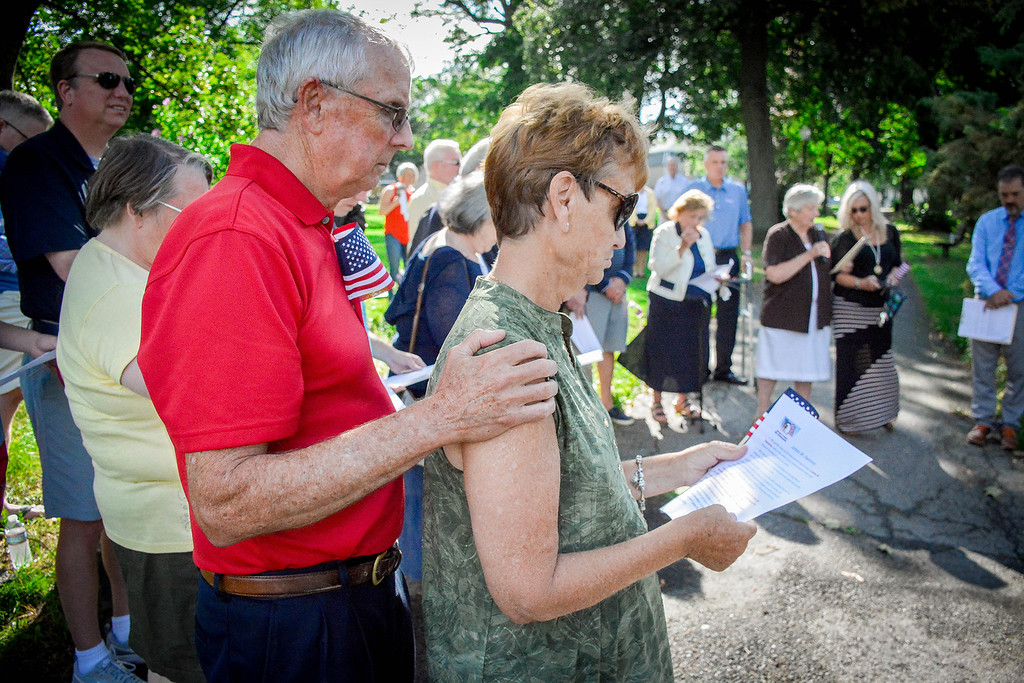 . At left, Mike Sullivan comforts his wife Donna who is the daughter of James W. Sweeney during the dedication ceremony in honor of him. SUN/Caley McGuane