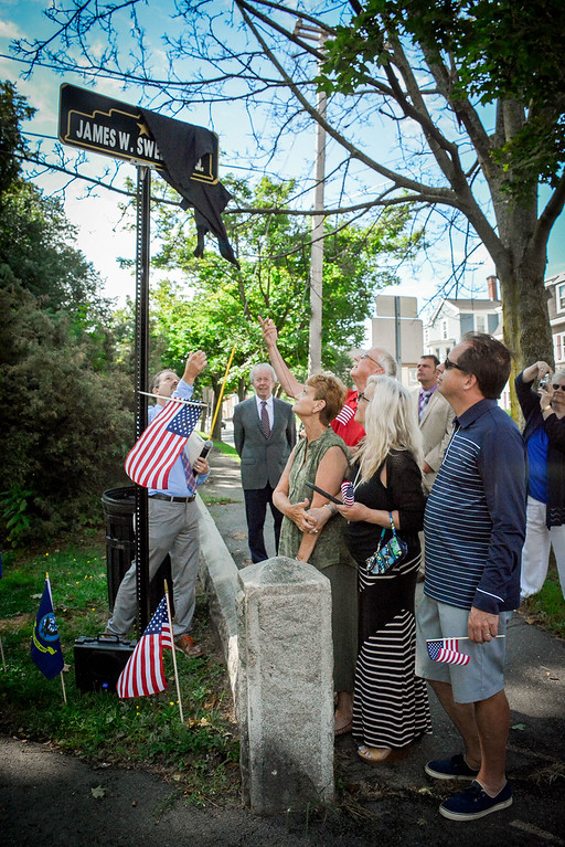 . At right, family members of James W. Sweeney help unveil the new sign in honor of him. James Sweeney\'s daughters, Donna Sullivan of Lowell and Kathy Sweeney LaBrecque of Pelham and their husbands, Mike Sullivan and Stuart LaBrecque. SUN/Caley McGuane