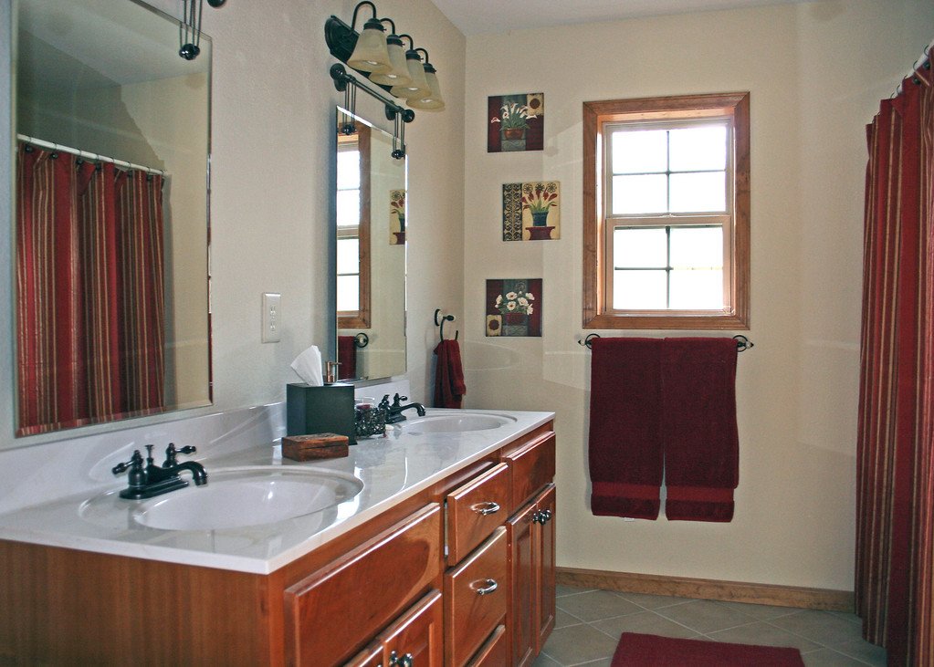 As you enter the master bathroom there is a linen closet to the right then the toilet and then the tub/shower.  The large counter has double sinks with plenty of storage.  There is even room at either end of the counter for a laundry hamper.