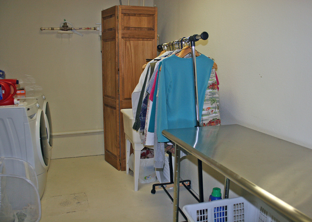 This is the downstairs laundry area which has a tub and is large enough to have a rod for clothes as well as a folding table.  There are also floor to ceiling shelves on the wall not seen that can be used for extra storage.