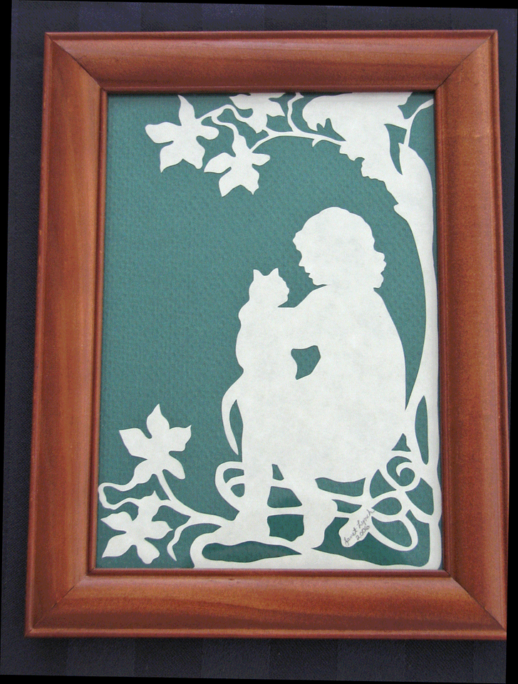 """Title: """"Girl Holding Cat (Positive)"""" - Framed Hand Cut Parchment <br /> Size: 5x7<br /> Price:$12 Plus Tax -S&H<br /> Email Your Order: JanetLynchArt@gmail.com"""
