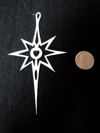 """Title: """"Guiding Star """" - Hand Cut Parchment<br /> Price: $6<br /> This item ships free in U.S. and Canada when shipped with an equal or lesser item<br /> <br /> ~ Scherenschnitte (hand paper cutting) Christmas Ornament<br /> Signed and dated by Janet Lynch<br /> <br /> ~ All Christmas ornaments can be personalized with names in Calligraphy<br /> Water Mark will not appear on your art order<br /> <br /> ~Want this as a print on a 5x7 Note Card? <a href=""""http://www.etsy.com/listing/71810088/note-cards-5x7-choose-any-photo-or-paper"""">http://www.etsy.com/listing/71810088/note-cards-5x7-choose-any-photo-or-paper</a><br /> <br /> ~ Want this as a print on a jewelry pendant? <a href=""""http://www.etsy.com/listing/74448914/cape-hatteras-lighthouse-fine-art"""">http://www.etsy.com/listing/74448914/cape-hatteras-lighthouse-fine-art</a><br /> <br /> ~ Special Custom requests welcome.....just email me and I will do my best to work with you. If you have a theme or particular interest I am sure I have a design for you......or I will design one just for you.<br /> <br /> ~Visit our shop to see all my hand cut Scherenschnitte Art, Fine Art Photography, Prints, Christmas Ornaments, Bookmarks, Note Cards, Photo Pendants, Jewelry:<br /> <a href=""""http://artgalleryriverrd.etsy.com"""">http://artgalleryriverrd.etsy.com</a>"""