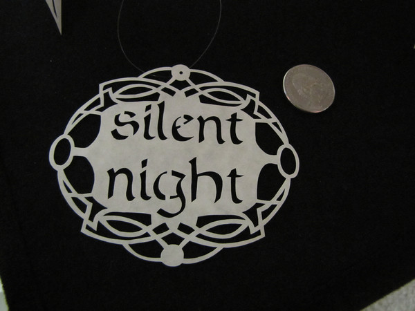 "Title: ""Silent Night "" - Hand Cut Parchment<br /> Price: $10<br /> This item ships free in U.S. and Canada when shipped with an equal or lesser item<br /> <br /> ~ Scherenschnitte (hand paper cutting) Christmas Ornament<br /> Signed and dated by Janet Lynch<br /> <br /> ~ All Christmas ornaments can be personalized with names in Calligraphy<br /> Water Mark will not appear on your art order<br /> <br /> ~Want this as a print on a 5x7 Note Card? <a href=""http://www.etsy.com/listing/71810088/note-cards-5x7-choose-any-photo-or-paper"">http://www.etsy.com/listing/71810088/note-cards-5x7-choose-any-photo-or-paper</a><br /> <br /> ~ Want this as a print on a jewelry pendant? <a href=""http://www.etsy.com/listing/74448914/cape-hatteras-lighthouse-fine-art"">http://www.etsy.com/listing/74448914/cape-hatteras-lighthouse-fine-art</a><br /> <br /> ~ Special Custom requests welcome.....just email me and I will do my best to work with you. If you have a theme or particular interest I am sure I have a design for you......or I will design one just for you.<br /> <br /> ~Visit our shop to see all my hand cut Scherenschnitte Art, Fine Art Photography, Prints, Christmas Ornaments, Bookmarks, Note Cards, Photo Pendants, Jewelry:<br /> <a href=""http://artgalleryriverrd.etsy.com"">http://artgalleryriverrd.etsy.com</a>"