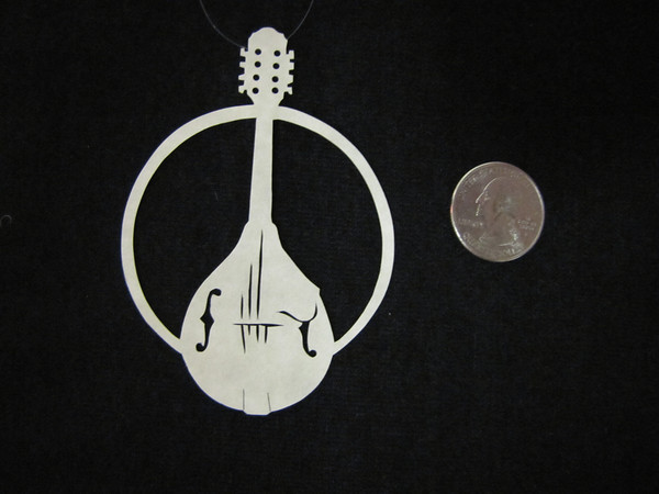 """Title: """" Mandolin """" - Hand Cut Parchment<br /> Price: $6<br /> This item ships free in U.S. and Canada when shipped with an equal or lesser item<br /> <br /> ~ Scherenschnitte (hand paper cutting) Christmas Ornament<br /> Signed and dated by Janet Lynch<br /> <br /> ~ All Christmas ornaments can be personalized with names in Calligraphy<br /> Water Mark will not appear on your art order<br /> <br /> ~Want this as a print on a 5x7 Note Card? <a href=""""http://www.etsy.com/listing/71810088/note-cards-5x7-choose-any-photo-or-paper"""">http://www.etsy.com/listing/71810088/note-cards-5x7-choose-any-photo-or-paper</a><br /> <br /> ~ Want this as a print on a jewelry pendant? <a href=""""http://www.etsy.com/listing/74448914/cape-hatteras-lighthouse-fine-art"""">http://www.etsy.com/listing/74448914/cape-hatteras-lighthouse-fine-art</a><br /> <br /> ~ Special Custom requests welcome.....just email me and I will do my best to work with you. If you have a theme or particular interest I am sure I have a design for you......or I will design one just for you.<br /> <br /> ~Visit our shop to see all my hand cut Scherenschnitte Art, Fine Art Photography, Prints, Christmas Ornaments, Bookmarks, Note Cards, Photo Pendants, Jewelry:<br /> <a href=""""http://artgalleryriverrd.etsy.com"""">http://artgalleryriverrd.etsy.com</a>"""