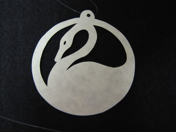 """Title: """"Swan """" - Hand Cut Parchment<br /> Price: $6<br /> This item ships free in U.S. and Canada when shipped with an equal or lesser item<br /> <br /> ~ Scherenschnitte (hand paper cutting) Christmas Ornament<br /> Signed and dated by Janet Lynch<br /> <br /> ~ All Christmas ornaments can be personalized with names in Calligraphy<br /> Water Mark will not appear on your art order<br /> <br /> ~Want this as a print on a 5x7 Note Card? <a href=""""http://www.etsy.com/listing/71810088/note-cards-5x7-choose-any-photo-or-paper"""">http://www.etsy.com/listing/71810088/note-cards-5x7-choose-any-photo-or-paper</a><br /> <br /> ~ Want this as a print on a jewelry pendant? <a href=""""http://www.etsy.com/listing/74448914/cape-hatteras-lighthouse-fine-art"""">http://www.etsy.com/listing/74448914/cape-hatteras-lighthouse-fine-art</a><br /> <br /> ~ Special Custom requests welcome.....just email me and I will do my best to work with you. If you have a theme or particular interest I am sure I have a design for you......or I will design one just for you.<br /> <br /> ~Visit our shop to see all my hand cut Scherenschnitte Art, Fine Art Photography, Prints, Christmas Ornaments, Bookmarks, Note Cards, Photo Pendants, Jewelry:<br /> <a href=""""http://artgalleryriverrd.etsy.com"""">http://artgalleryriverrd.etsy.com</a>"""