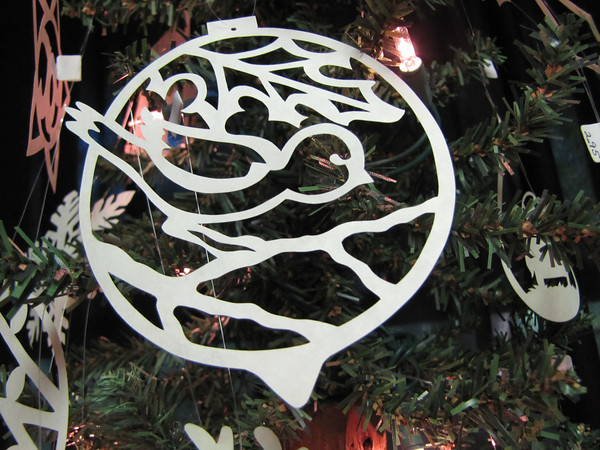 """Title: """"Bird and Holly """" - Hand Cut Parchment<br /> Price: $10<br /> This item ships free in U.S. and Canada when shipped with an equal or lesser item<br /> <br /> ~ Scherenschnitte (hand paper cutting) Christmas Ornament<br /> Signed and dated by Janet Lynch<br /> <br /> ~ All Christmas ornaments can be personalized with names in Calligraphy<br /> Water Mark will not appear on your art order<br /> <br /> ~Want this as a print on a 5x7 Note Card? <a href=""""http://www.etsy.com/listing/71810088/note-cards-5x7-choose-any-photo-or-paper"""">http://www.etsy.com/listing/71810088/note-cards-5x7-choose-any-photo-or-paper</a><br /> <br /> ~ Want this as a print on a jewelry pendant? <a href=""""http://www.etsy.com/listing/74448914/cape-hatteras-lighthouse-fine-art"""">http://www.etsy.com/listing/74448914/cape-hatteras-lighthouse-fine-art</a><br /> <br /> ~ Special Custom requests welcome.....just email me and I will do my best to work with you. If you have a theme or particular interest I am sure I have a design for you......or I will design one just for you.<br /> <br /> ~Visit our shop to see all my hand cut Scherenschnitte Art, Fine Art Photography, Prints, Christmas Ornaments, Bookmarks, Note Cards, Photo Pendants, Jewelry:<br /> <a href=""""http://artgalleryriverrd.etsy.com"""">http://artgalleryriverrd.etsy.com</a>"""