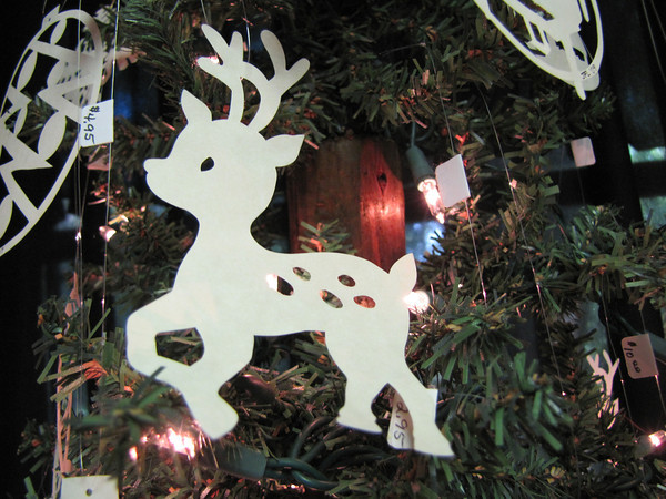 """Title: """"Reindeer"""" - Hand Cut Parchment<br /> Price: $6<br /> This item ships free in U.S. and Canada when shipped with an equal or lesser item<br /> <br /> ~ Scherenschnitte (hand paper cutting) Christmas Ornament<br /> Signed and dated by Janet Lynch<br /> <br /> ~ All Christmas ornaments can be personalized with names in Calligraphy<br /> Water Mark will not appear on your art order<br /> <br /> ~Want this as a print on a 5x7 Note Card? <a href=""""http://www.etsy.com/listing/71810088/note-cards-5x7-choose-any-photo-or-paper"""">http://www.etsy.com/listing/71810088/note-cards-5x7-choose-any-photo-or-paper</a><br /> <br /> ~ Want this as a print on a jewelry pendant? <a href=""""http://www.etsy.com/listing/74448914/cape-hatteras-lighthouse-fine-art"""">http://www.etsy.com/listing/74448914/cape-hatteras-lighthouse-fine-art</a><br /> <br /> ~ Special Custom requests welcome.....just email me and I will do my best to work with you. If you have a theme or particular interest I am sure I have a design for you......or I will design one just for you.<br /> <br /> ~Visit our shop to see all my hand cut Scherenschnitte Art, Fine Art Photography, Prints, Christmas Ornaments, Bookmarks, Note Cards, Photo Pendants, Jewelry:<br /> <a href=""""http://artgalleryriverrd.etsy.com"""">http://artgalleryriverrd.etsy.com</a>"""