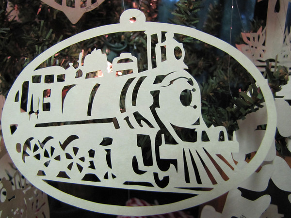 "Title: "" Train "" - Hand Cut Parchment Price: $10 This item ships free in U.S. and Canada when shipped with an equal or lesser item  ~ Scherenschnitte (hand paper cutting) Christmas Ornament Signed and dated by Janet Lynch  ~ All Christmas ornaments can be personalized with names in Calligraphy Water Mark will not appear on your art order  ~Want this as a print on a 5x7 Note Card? http://www.etsy.com/listing/71810088/note-cards-5x7-choose-any-photo-or-paper  ~ Want this as a print on a jewelry pendant? http://www.etsy.com/listing/74448914/cape-hatteras-lighthouse-fine-art  ~ Special Custom requests welcome.....just email me and I will do my best to work with you. If you have a theme or particular interest I am sure I have a design for you......or I will design one just for you.  ~Visit our shop to see all my hand cut Scherenschnitte Art, Fine Art Photography, Prints, Christmas Ornaments, Bookmarks, Note Cards, Photo Pendants, Jewelry: http://artgalleryriverrd.etsy.com"