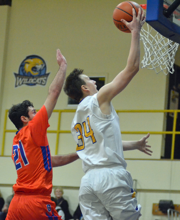 . KYLE MENNIG - ONEIDA DAILY DISPATCH Cazenovia\'s Kevin Stalder (34) lays the ball in the basket in front of Oneida\'s Vinny Leibl (21) during their game in Cazenovia, N.Y., on Saturday, Jan. 14, 2017.