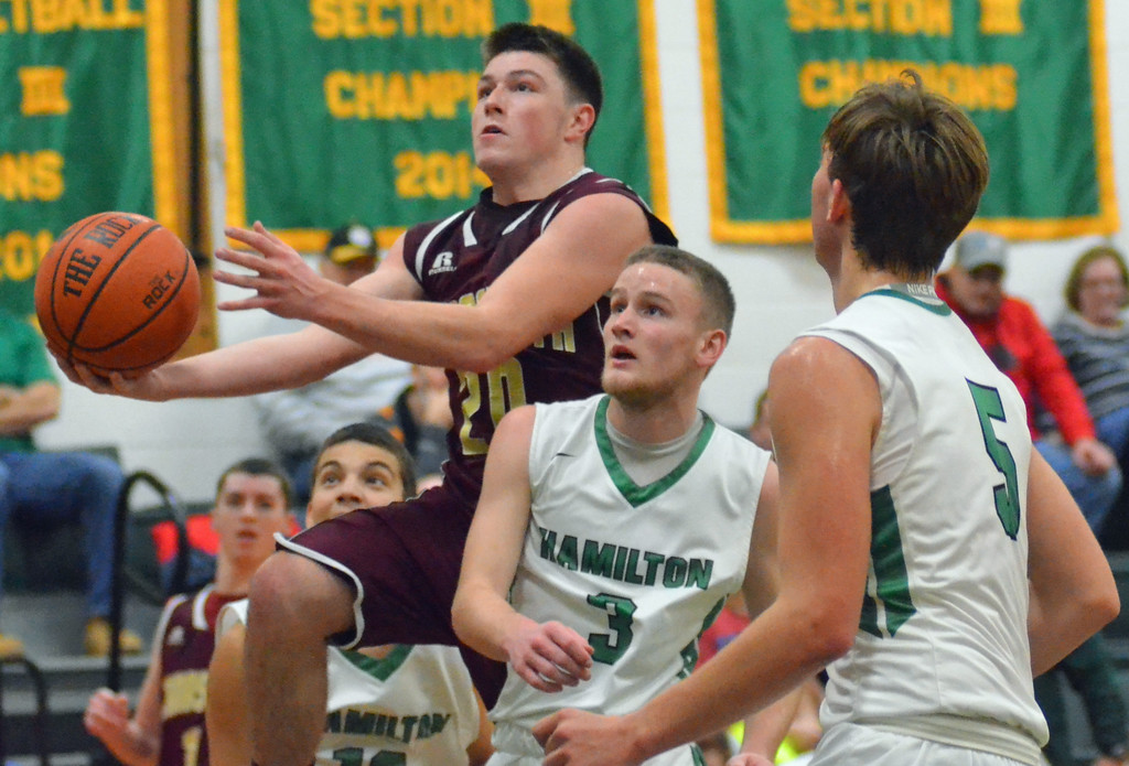 . KYLE MENNIG - ONEIDA DAILY DISPATCH Canastota\'s Jeff Marsh (20) goes up for a layup as he is fouled by Hamilton\'s Sean Hunt (3) during their game in Hamilton on Friday, Jan. 13, 2017. Also pictured is Hamilton\'s Michael Hershey (5).