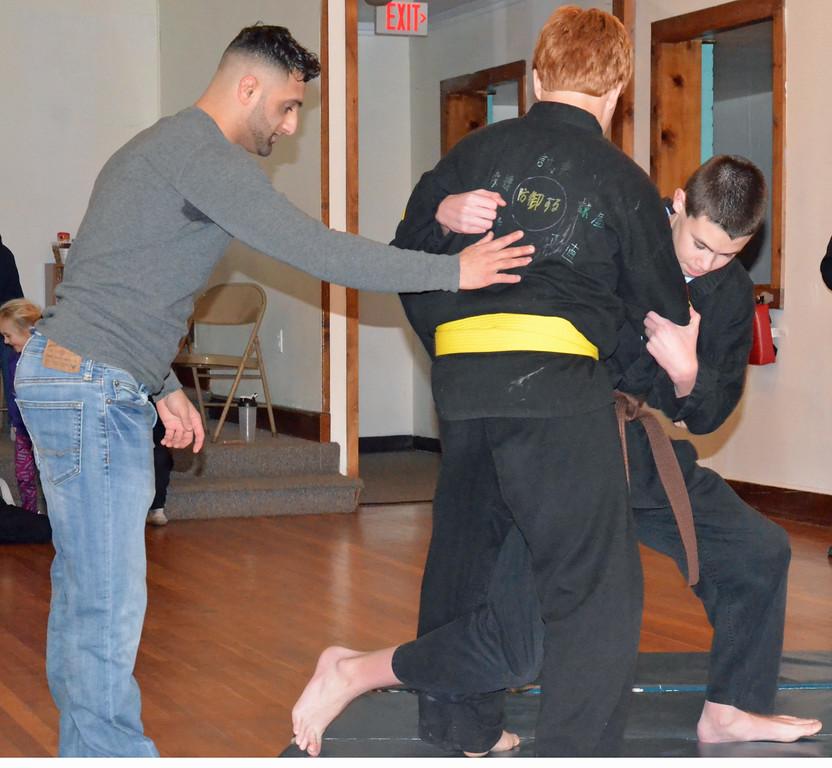 . KYLE MENNIG - ONEIDA DAILY DISPATCH Josh Ricci, left, walks Robert Merrill, right, and Randy Williamson through an inside top takedown at Waterman\'s Martial Arts Ryouzan Dojo in Oneida, N.Y. on Thursday, Jan. 19, 2017.