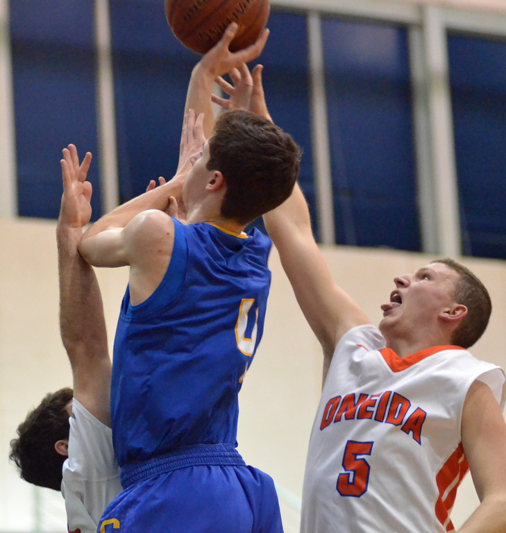 . KYLE MENNIG - ONEIDA DAILY DISPATCH Oneida\'s Jeffrey Coulter (5) comes in from behind to block a shot by Cazenovia\'s Thomas Bragg (4) during their game in Oneida on Wednesday, Jan. 25, 2017. Also defending on the play is Oneida\'s Vinny Leibl.