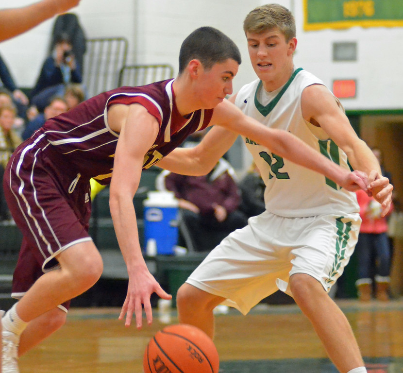 . KYLE MENNIG - ONEIDA DAILY DISPATCH Canastota\'s Mike Bigos (1) puts down a dribble as Hamilton\'s Trevor Dow (12) defends during their game in Hamilton on Friday, Jan. 13, 2017.