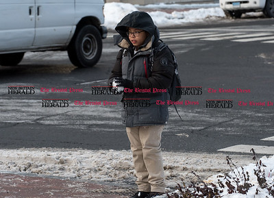 010917  Wesley Bunnell | Staff  A youngster stops to form a snowball before crossing the street at Main & West Main St on Monday afternoon.
