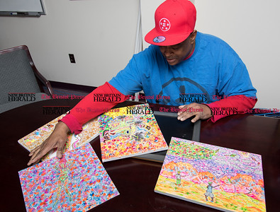010917  Wesley Bunnell | Staff  New Britain resident Gerald Filyaw started a company named The Miracle of Loaves N Fish, which features a bible-based logo in order to inspire hope. Gerald shows pieces of his original artwork.