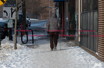 010917  Wesley Bunnell | Staff  A man walks up a snow covered sidewalk on Main St on Monday afternoon.