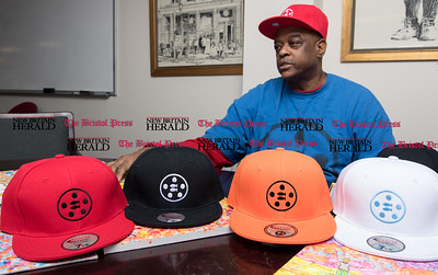 010917  Wesley Bunnell | Staff  New Britain resident Gerald Filyaw started a company named The Miracle of Loaves N Fish, which features a bible-based logo in order to inspire hope.  Several different color hats with the Loaves N Fish design sit on the desk during his recent interview.