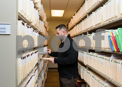 011317  Wesley Bunnell | Staff  New Britain Police Detective Dave McDermott looks through case files from 2008 in the record room on Friday afternoon.