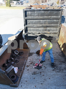 011317  Wesley Bunnell | Staff  New Britain recycling center operator Kris Caliskan scoops up metal items that have fallen around a recycling dumpster on Friday afternoon.