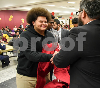013017 Wesley Bunnell | Staff  New Britain High School held a Friends of Football 2016 Season Awards Ceremony on Monday evening in the NBHS cafeteria. Senior John Martinez receives a sweatshirt from assistant coach and President of Friends of Football Carlos Blanco.