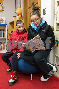 013017 Wesley Bunnell | Staff  Michelle Quiros assists her son Elijah, age 8, in reading the book If You Give a Pig a Party in the childrens section of the New Britain Public Library on Monday evening.