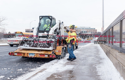 011017  Wesley Bunnell | Staff  Workers from the CT DOT finished clearing snow from the Harry Truman Overpass in New Britain on Tuesday afternoon. Stacy Asberry loads the Bobcat Steer Loader onto a trailer with the help of co-worker Jose Santiago.