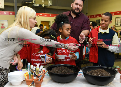 011117  Wesley Bunnell | Staff  Volunteers from Comcast along with Nutmeg Big Brothers Big Sisters held a luncheon on Wednesday afternoon at Comcast in Berlin. Mentor Christine Quiterio, left, hands potted plants to decorate to Christian, age 9 as his mentor Jay looks over his shoulder.