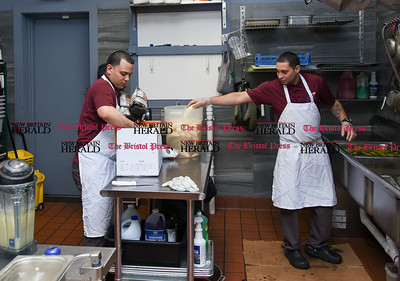 011117  Wesley Bunnell | Staff  Chef Josue Lopez of Criollisimo Restaurant , shown left, gathers ingredients as Julio Suarez peels and preps plantains.
