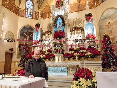 011217  Wesley Bunnell | Staff  Msgr. Daniel J. Plocharczyk stands inside Sacred Heart Church on Thursday afternoon at the altar of sacrifice with the altar of reservation decorated for Christmas in the background
